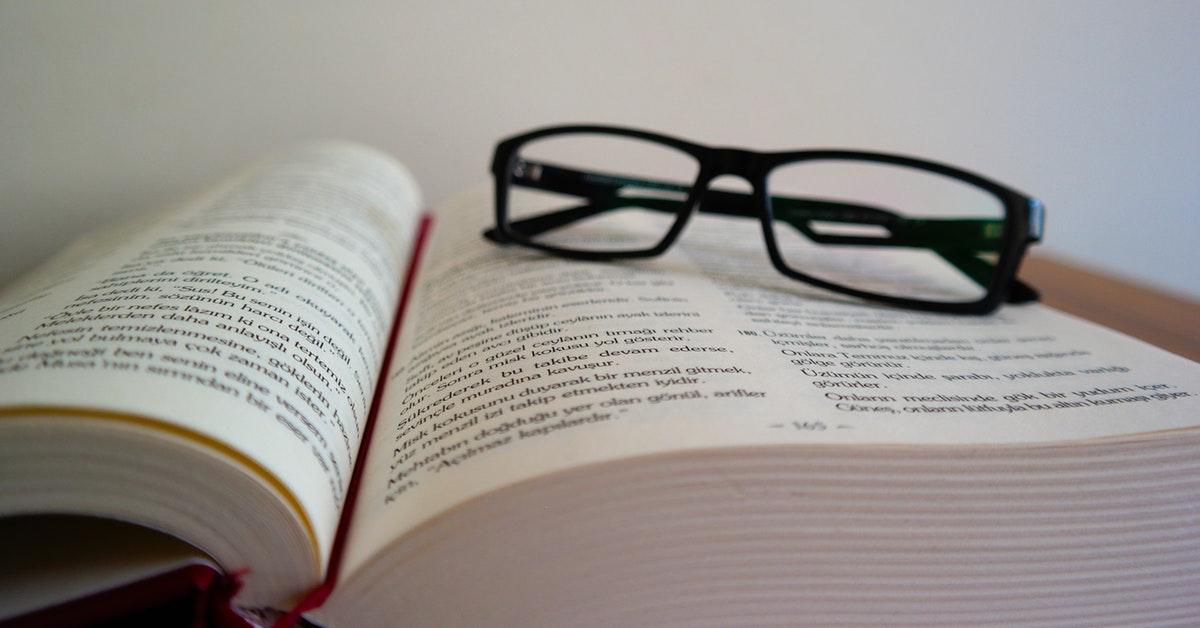 occhiali su libro di docente che attende il decreto salvaprecari bis.